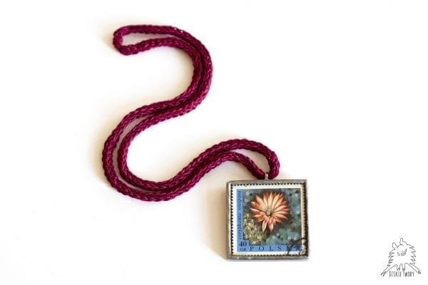 Kwadratowy wisiorek ze szkła ze starym znaczkiem pocztowym ilustrującym kwiat. Naszyjnik na bordowym łańcuszku.