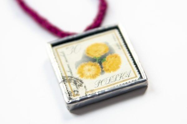 Dzikie Twory - naszyjnik ze znaczkiem pocztowym kwiat centuria zbliżenie