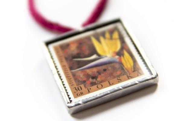 Dzikie Twory - naszyjnik ze znaczkiem pocztowym kwiat strelizia zbliżenie