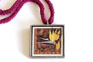 Dzikie Twory naszyjnik ze znaczkiem pocztowym strelicja królewska zbliżenie na detal.